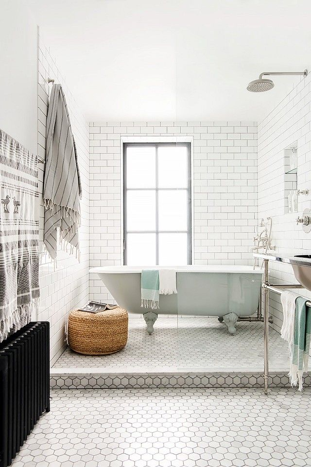 Bathroom with floor to ceiling tile and a baby blue clawfoot tub