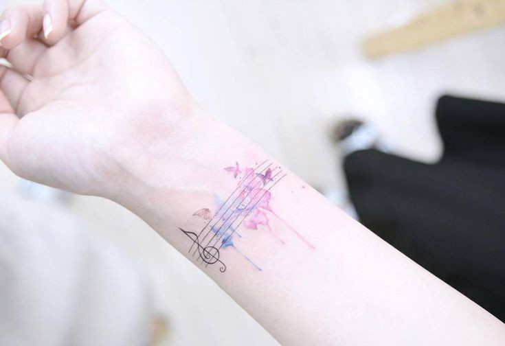 Butterfly music staff tattoo on the left inner wrist.