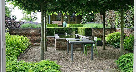 http://www.tuindesign-ten-horn.nl Tuinarchitect - tuinontwerp. Landelijke tuin met keermuurtjes om hoogteverschillen op te vangen, een vijver en aansluitend een intiem terras onder dakbomen (Limburg).