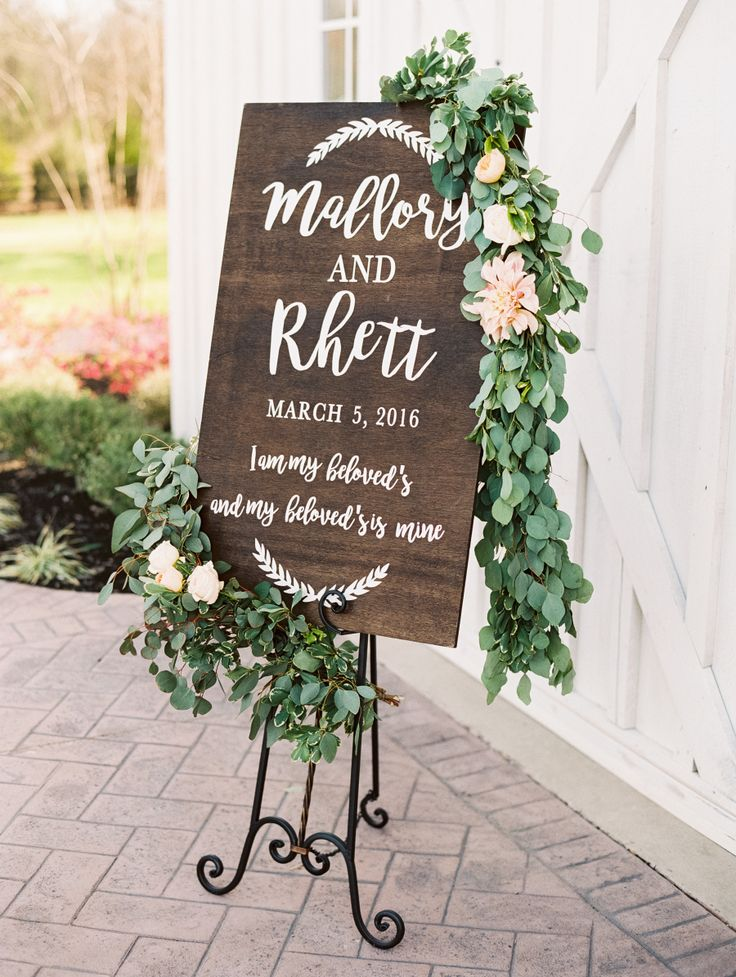 Rustic wooden wedding sign covered in eucalyptus garland. Photography : Becca Lea Read More on SMP: http://www.stylemepretty.com/2016/08/05/a-mega-chic-black-tie-wedding-in-a-barn/