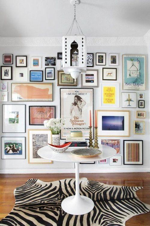 Decoração com mesa tulipa, tapete de zebra e parede com muitos quadros, gallery wall