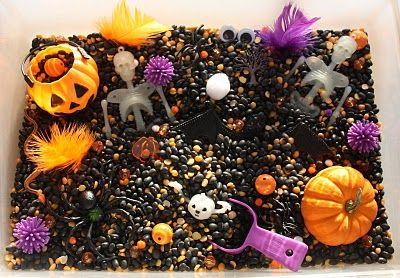 Halloween Sensory Tub- Here's what's inside:    :: Black beans  :: Yellow lentils  :: Porcupine balls  :: Real mini pumpkin  :: Plastic pumpkin  :: Purple scoop  :: Skeletons  :: Various beads  :: Teeny tiny pom poms  :: Stretchy spiders, a snake and a big bat  :: Googly eyes  :: A few scrapbooking embellishments  :: Feathers