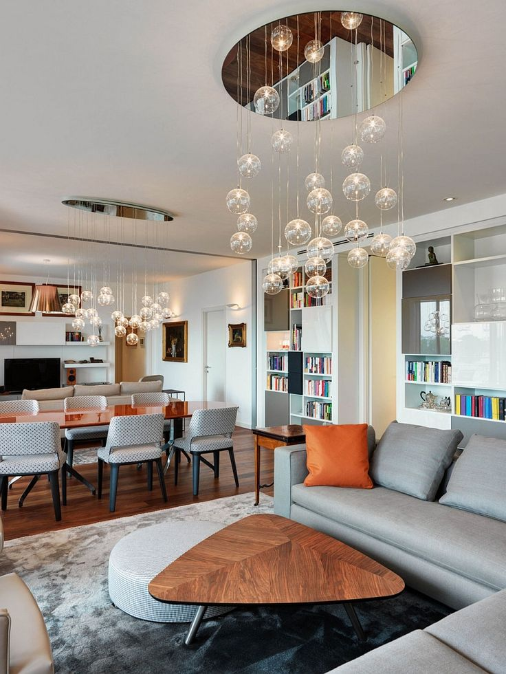 Apartments:Modern Interior Design Living Room With Surprising Cascading Chandeliers Also Wooden Coffee Table Also Sofas Cushions Rugs Also Dining Sets Also Smart Shelves With Colorful Books Modern Interior Design of Luxury Apartment in Milan To Inspire You