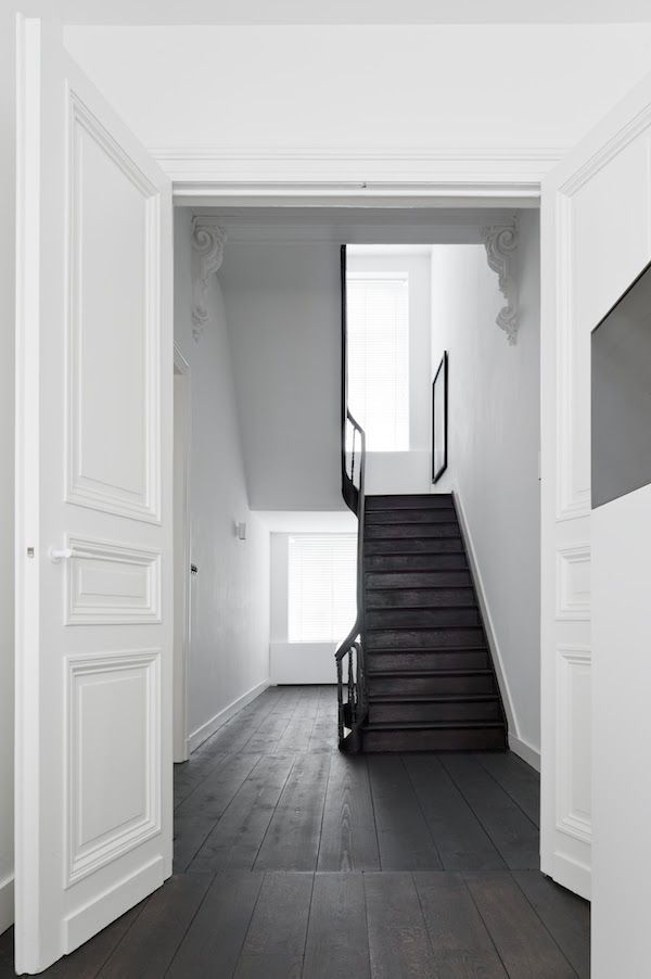 Beautiful black staircase surrounded by all white surfaces.