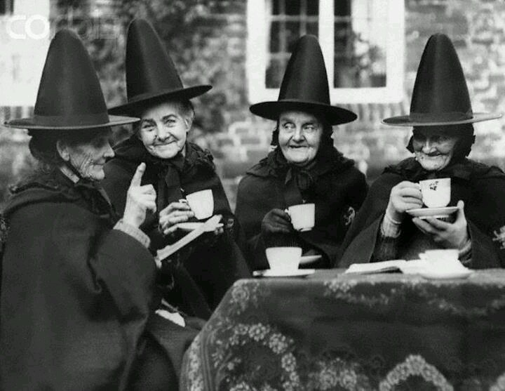 """Shot of the """"witches tea party"""" we posted earlier. They are actually members of The Hospital of Holy and Undivided Trinity at Castle Rising, Norfolk, England, founded by Henry Howard, Earl of Northampton, in 1610. The foundation provides for a governess and 12 sisters. Here four of the ladies are enjoying their afternoon tea. ca. 1929 Image © Hulton-Deutsch Collection"""
