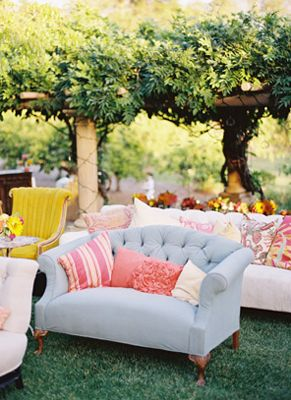 Set up a lounge area with plush sofas, loveseats, eclectic chairs, and a collection of pillows for guests to be comfortable and hangout after the ceremony, and during the reception.
