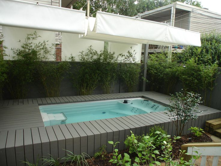 This Endless Pools Swim Spa is recessed into its deck for an in-ground appearance. Overhead, sailcloth slides for shade or a full sky view. For a Free Idea Kit, visit www.endlesspools.com.