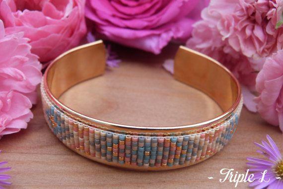~ DESCRIPTIF ~ Ce bracelet manchette LUCILE est composé dun tissage fait main avec des perles de verre Miyuki et dune manchette en laiton doré. Couleurs des perles : saumon - gris - bleu - doré - pêche. Dimensions : 1.9 cm de large. ~ MATERIEL UTILISE ~ - Perles de verre japonaises Miyuki - Manchette en laiton doré - origine : Europe  ~ ENVOI ~ Les bijoux sont envoyés en courrier suivi dans une enveloppe en papier bulle et soigneusement emballés.  ~ PRECAUTIONS DUSAGE ~ Ce bijou est fait à…