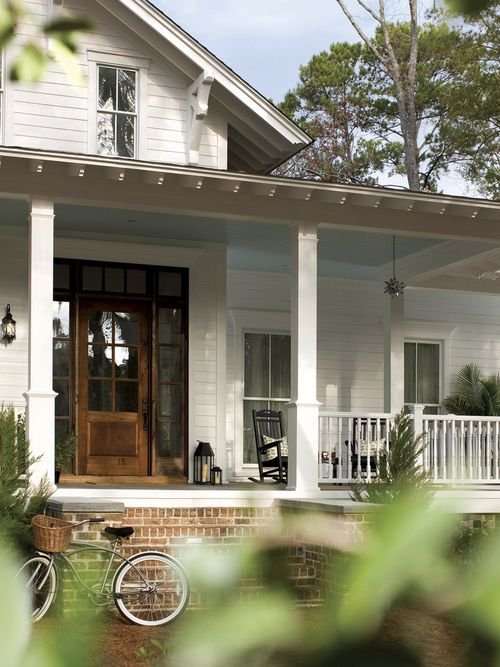 Little white house, brick steps, dormer, wide wood front door, big front porch with rocking chair.