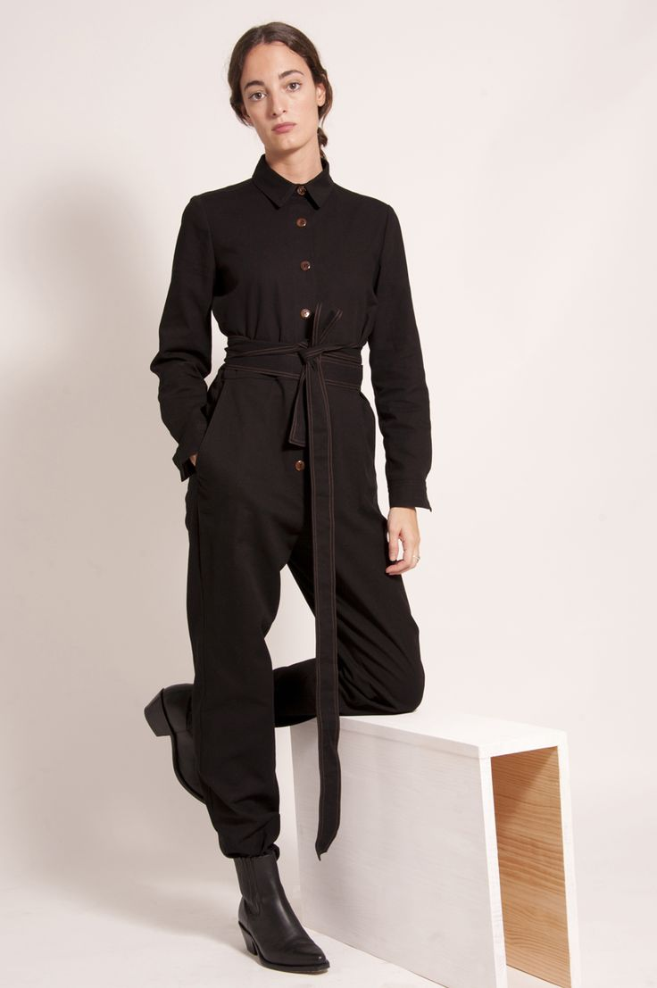 Black belted waist jumpsuit in black cotton. Shirt collar and long sleeves. Two pockets on the hips and two on the back.  Size S measurements: Length 1,47cm - Armpit to armpit 49cm - Shoulder to shoulder 38cm.  Size M measurements:Length 1,52cm- Armpit to armpit 49,5cm - Shoulder to shoulder 40cm.  100% cotton.  Made in Spain