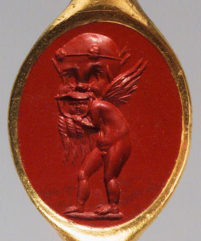 Amor mit einer Silensmaske. Römisch, 1. Jh. n. Chr. Jaspis, rot. In antikem Goldring, die Rückseite geschlossen. H. 1,57 cm, B. 1,23 cm. Amor hat eine große Silensmaske mit Kranz, spitzen Ohren und langem Bart aus Korkzieherlocken übergestülpt und blickt mit ernster Miene aus dem offenen Mund der Maske heraus. I Kunsthistorisches Museum Wien