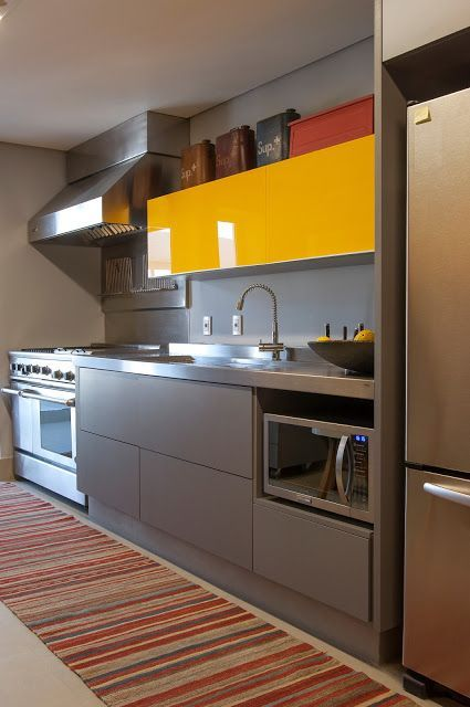 Referência de combinação de materiais e cores: bancada de inox + gavetas marrons + armários amarelos.:
