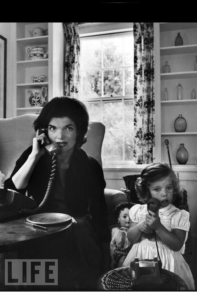 Jackie talks on the telephone as Caroline mimics her on a toy phone, at home in Hyannisport, Mass., Sept. 30, 1960.