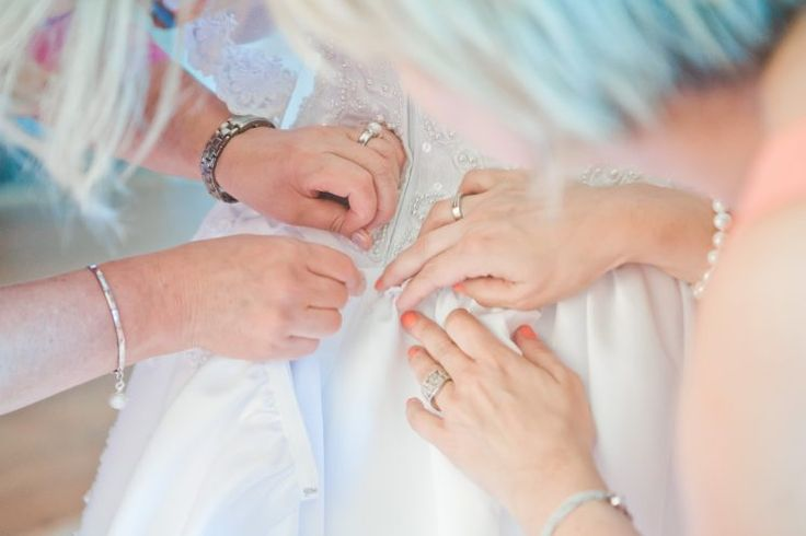 So many hands to wear a the wedding dress.