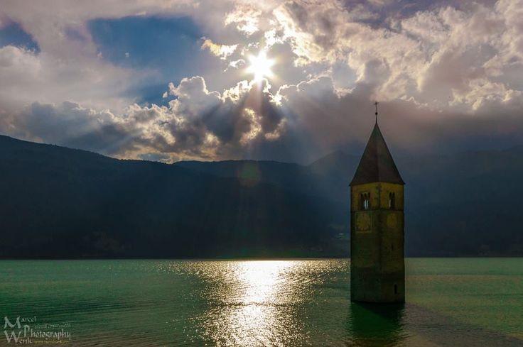 The sunken church tower of Graun at Lake Reschensee (Italian: Lago di Resia) in South Tyrol, Italy