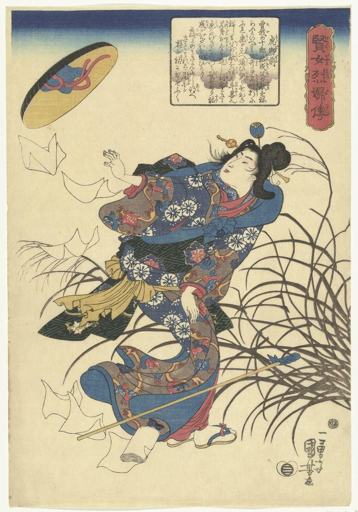 Tora gozen, staand bij struik in harde wind, omkijkend naar haar wegwaaiende hoed