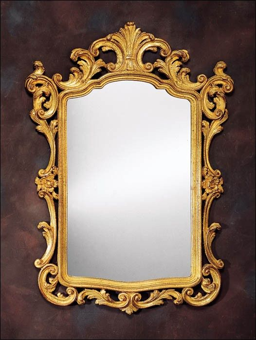This lovely wall mirror features an 18th century Venetian style. The mirror is carved from wood and features leaf and scroll design. It is finished in antiqued gold leaf. The mirror measures 31