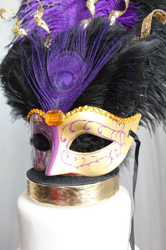 Over The Top Cake Topper offers a unique variety of unusual, custom cake toppers for any type of party, Wedding, Quinceanera, Sweet Sixteen, birthday, graduation, New Year's, Ball and all other celebrations and themes!  Top your Venetian, Paris or Mardi Gras cake with this elegant Purple and Gold glittery and rhinestone masquerade mask cake topper. The mask sits on a black and gold base. The black and purple ostrich feathers along with the gold sparklers and purple peacock feather give the…