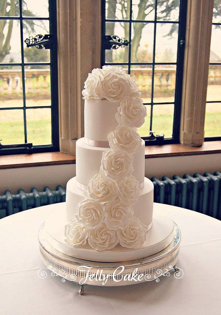 An all white wedding cake with just a hint of beige with the ribbon. Decorated with a cascade of large white sugar roses. Set up at the very lovely Coombe Lodge at Blagdon.