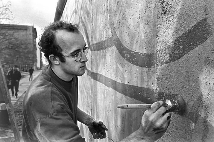 Keith Haring pintando o muro de Berlim próximo ao Checkpoint Charlie em 1986.