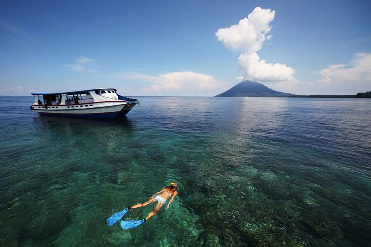young-woman-snorkeling-in-transparent-shallow-sea-near-boat-in-Manado-Indonesia-1600x1066.jpg (1600×1066)