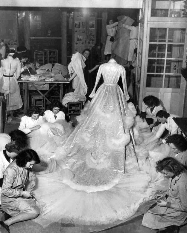 Christian Dior Atelier 1951.Seamstresses finishing the #weddinggown for Princess Soraya who married the Shah of Iran in 1951. The dress consisted of 27 yds of silver lame, 20,000 feathers and 6000 diamond pieces. #vintagewedding #50sweddingdress