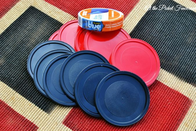 scotch blue tape outdoor checker board project  -Get sturdy fabric, painters tape, tupperware lids, and red/black paint.
