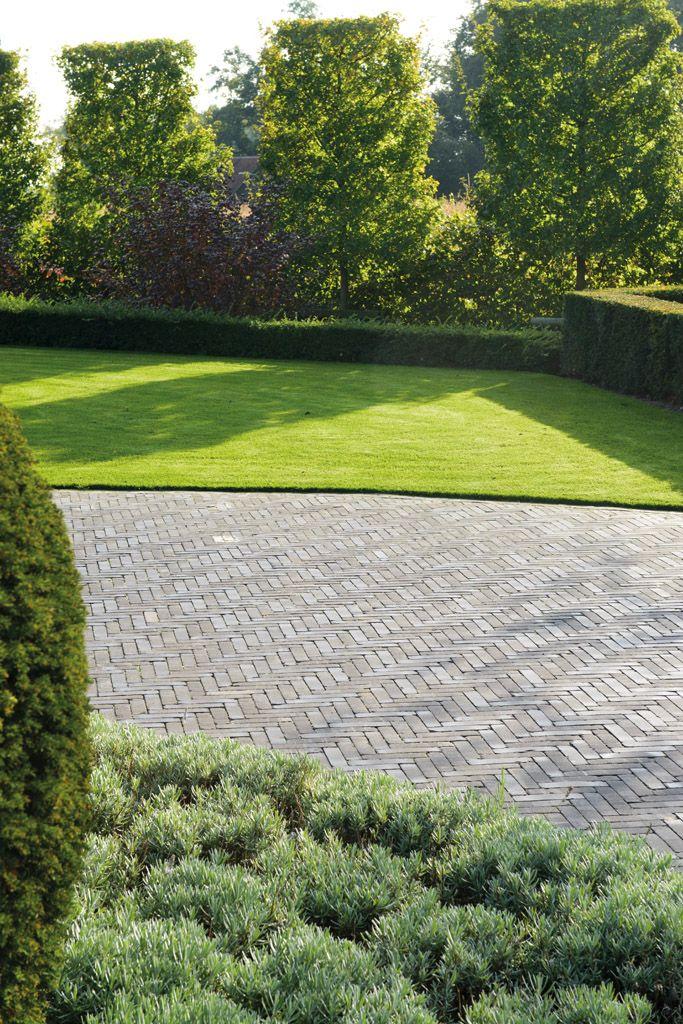 Strakke, groene tuin met een oprit van Terra Lucca Antica gebakken klinkers van Bylandt