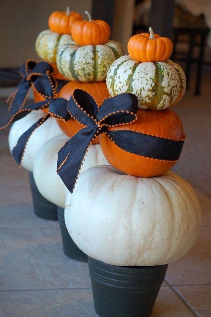 """des """"piliers"""" de citrouilles en blanc et orange décorés de nœuds noirs"""