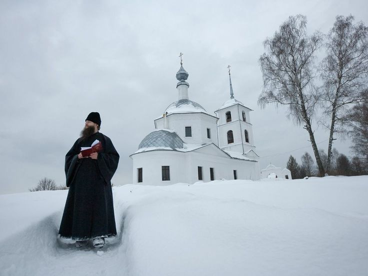 Russian Orthodox Church in the background with a Priest walking in the fresh snowfall.