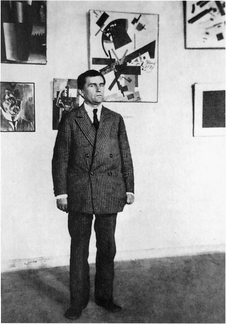 Kazimir Malevich stands in front of a few of his paintings. Leningrad, 1920s.