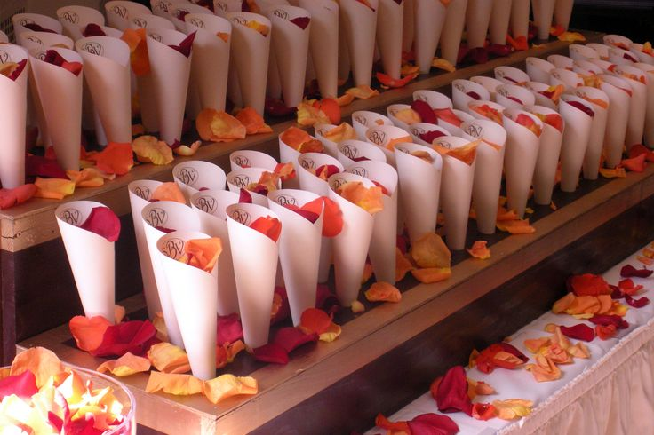 Have your guests shower you with the scent of fresh roses! A custom built petal cone holder with coordinating petal launching cones sits amongst shimmering table decor.vendors: DEsigns for all times