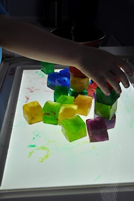 ice cubes colored with food coloring...fill large clear plastic container with Christmas lights (that makes your light table), then let child play/ build with ice cubes on the light table