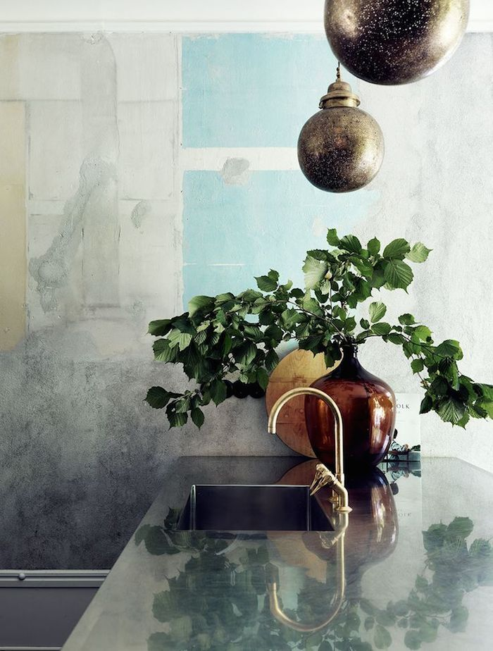 Kitchen: stainless steel benchtop and built-in moulded sink, gold/brass mixer tapware, indoor plant, amber glass vase, pale blue wall art, bronze orb pendants