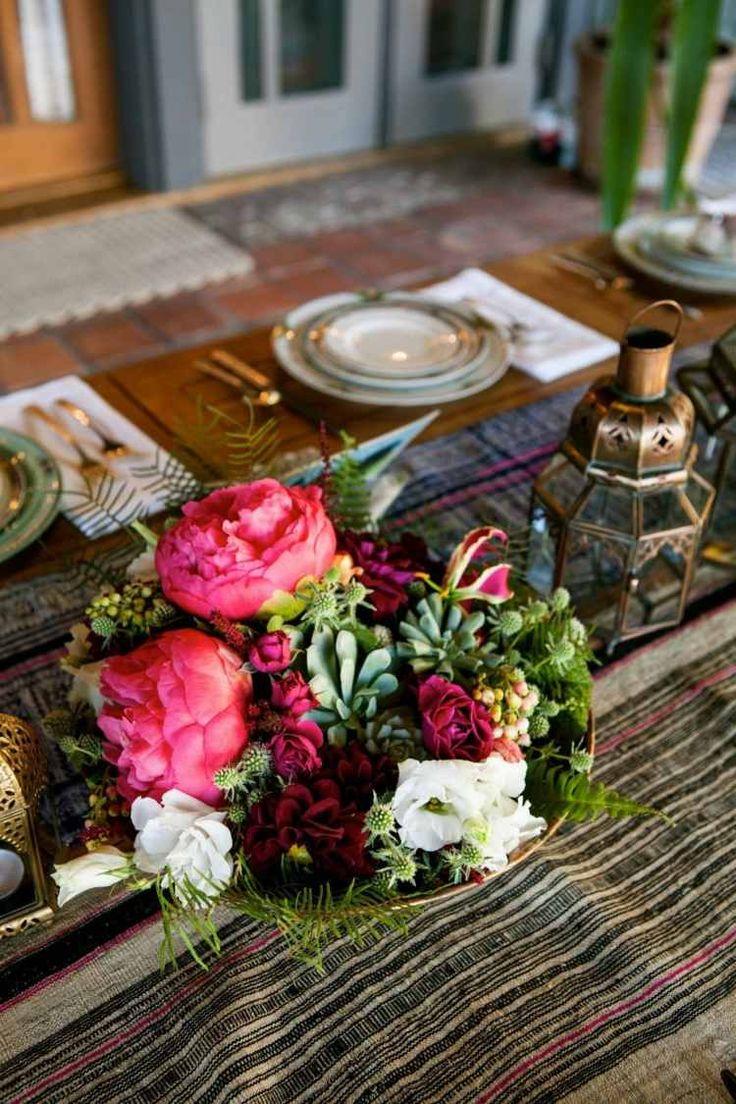 centre de table floral en pivoines roses, roses blanches et plantes succulentes dans un panier