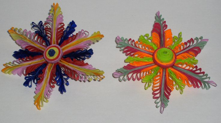 "Quilled paper flowers which can be hung as ornaments. they also spins like tops - 3"" diameter. $10.00 ea. - the one with the bright green has sold."