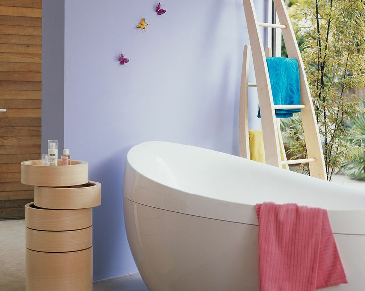 Associez le lilas clair à des touches de couleur vive. La simplicité de cette baignoire sur pied contemporaine et des meubles en bois clair est soulignée par les murs lilas et les vives touches de couleurs sucrées.