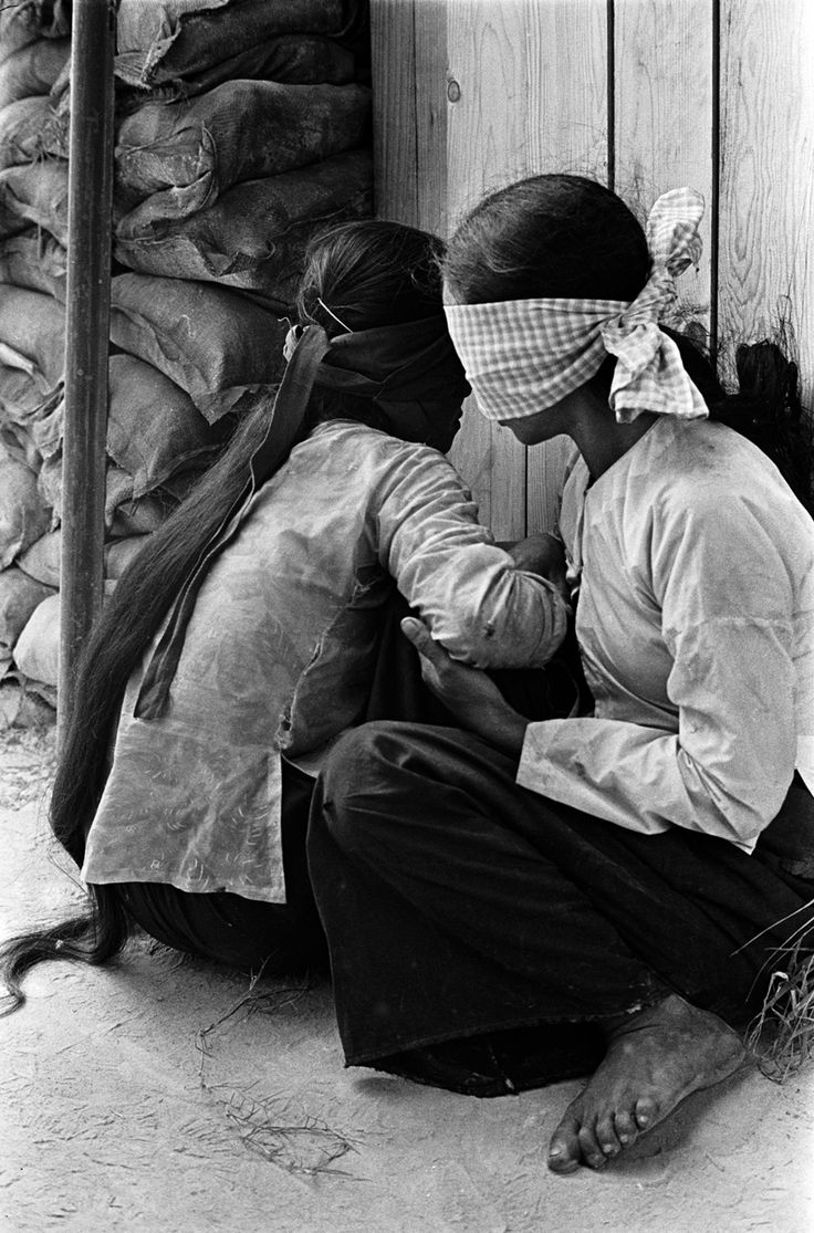 Blindfolded detainees await questioning from a US Army interpreter. Names, date, and location unknown. Charlie Haughey