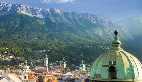 Von Süden aus blückt man über Innsbruck auf die Nordkette des Karwendels. In der Mitte des Bildes Recken sich dei Türme des Alten Rathauses und des Insbrucker Doms gen Himmel.  (Foto: Innsbruck Tourismus)
