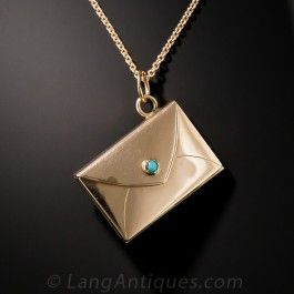 The world's smallest golden purse (3/4 by 9/16 inch), set with a tiny turquoise clasp, opens up and folds out to reveal a double locket compartment (currently occupied by a handsome Victorian couple). From late-19th century Great Britain, crafted in 9ct. rosy-yellow gold, with new 18 inch 14K chain.