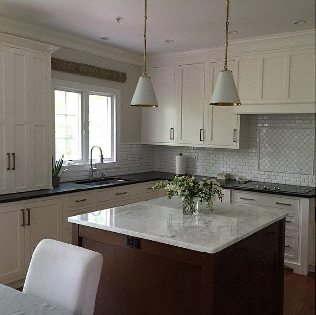 White Dove OC-17 Benjamin Moore Kitchen cabinet. Perimeter counter leathered black granite.  The cherry wood island measures 51″ square and is topped with Mont Blanc marble.