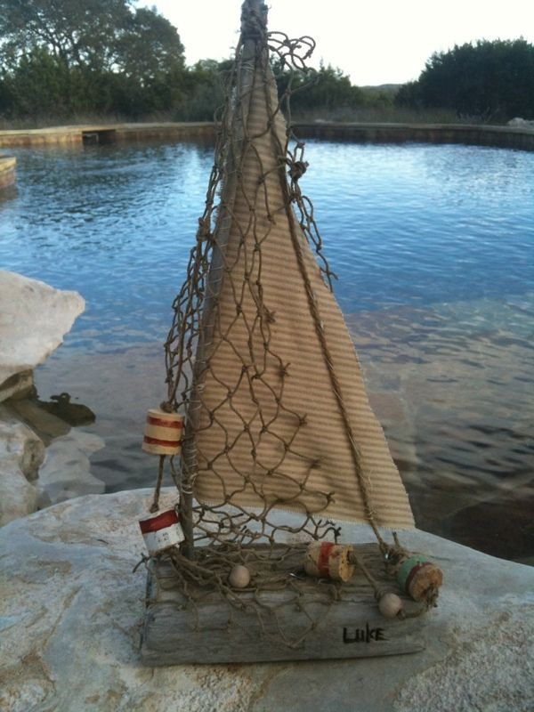 Driftwood sailboat with wine cork buoys.