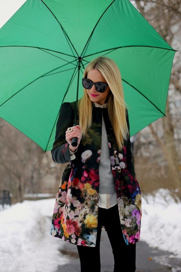 Floral printed black raincoat, grey long sleeve cardigan, white blouse, black pants.