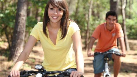 Image of young woman and man bicycling