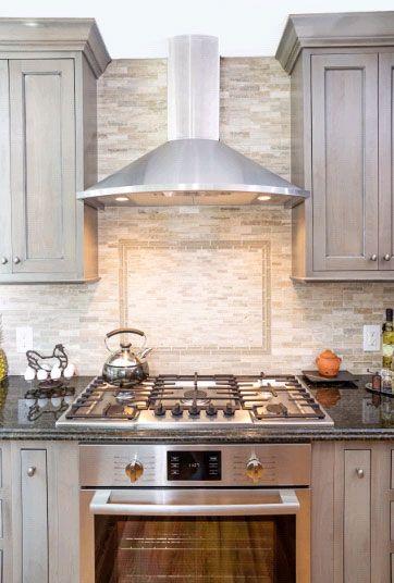 Mosaic backsplash with framed tile design above cooktop