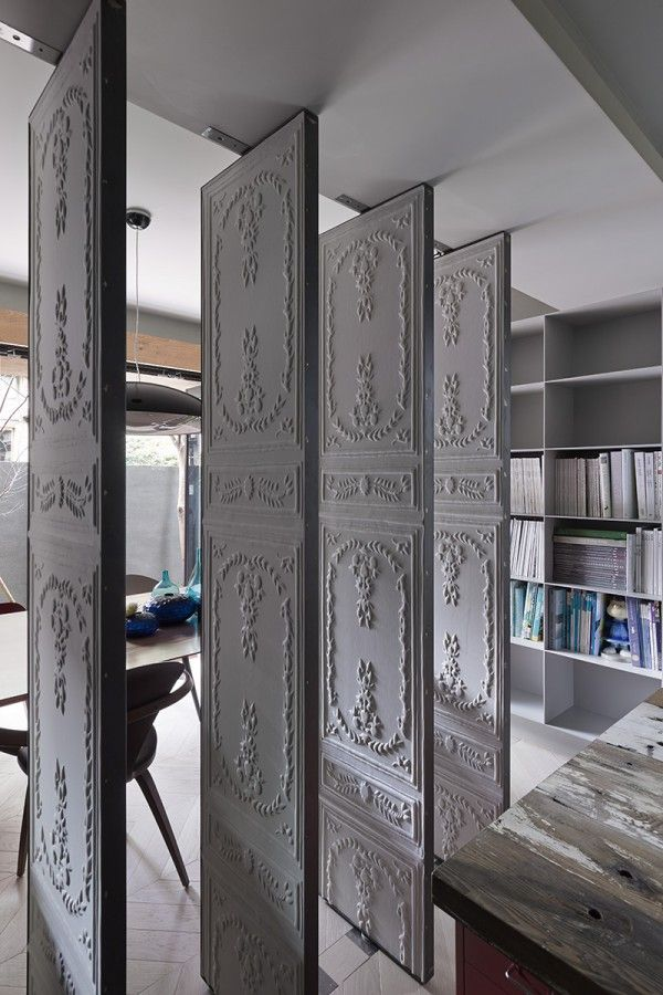 Of particular interest are the way in which Ganna Studio has chosen to separate these rooms. Embossed wallpaper panels divide a contained workspace from the dining area and kitchen, effectively separating work from play and brining an ornate, classic element to the interior. Spin the panels and close the space.