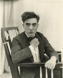 """Sessue Hayakawa sits in a chair with his fist raised in a publicity still for """"His Birthright"""" (Haworth 1918). Wisconsin Historical Society Image ID: 68692"""