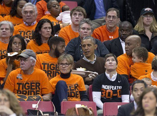 Barack Obama, Avery Robinson, Malia Obama, Craig Robinson | President Barack Obama's nephew Avery Robinson, left, offers some of his food to his uncle as they attend the Princeton vs Wisconsin-Green Bay women's college basketball game in the first round of the NCAA tournament in College Park, MD, March 21 2015. Also attending are Obama's daughter Malia Obama, far left, and his brother-in-law Craig Robinson, right. Obama's neice Leslie Robinson, plays for Princeton.