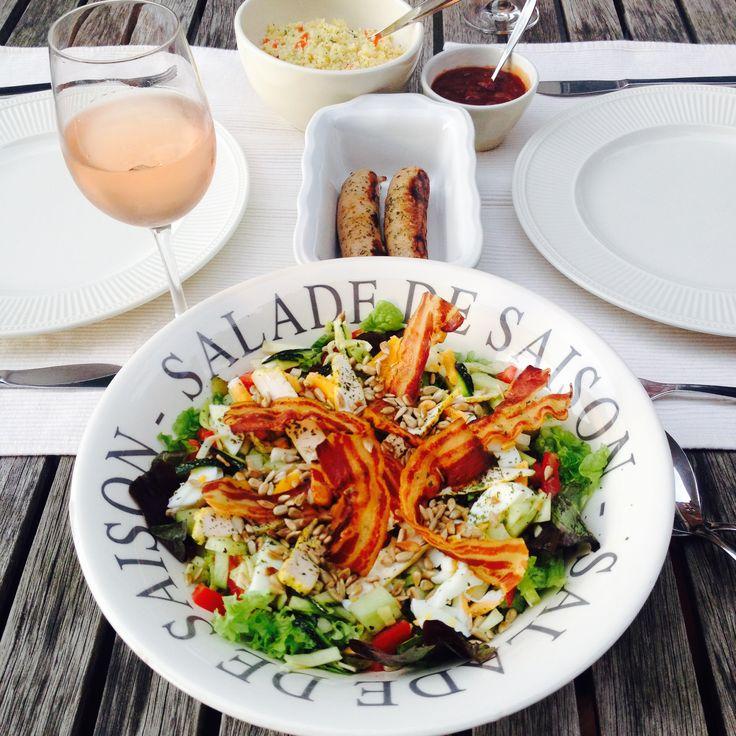 Salade de saison;  reepjes rauwe courgette, komkommer, gegrilde kip, ontbijtspekjes uitgebakken in oven, geroosterde zonnebloempitjes, gekookt eitje, tomaatje, augurkje, olijfolie, citroensap, honing, zout en peper   Grilworstjes met couscoussalade