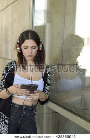 Young beautiful girl browsing a tablet and listening to the music with headphones